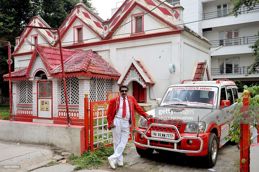In this photograph taken on July 26, 2014, Indian businessman Sevenraj who has a fixation for the colours red and white poses outside his residence in Bangalore. 52-year-old Sevenraj's fetish for red and white colours started several decades ago with an intention to create a unique identity for himself and a brand image for his real estate agency went on to become a part and parcel of his life, his home and his family. Born as the seventh offspring, his realist father named him 'Sevenraj' and thus the number '7' too has remained his other fixation apart from the 'Red & White' colours. Everything in his house, office, his car are of the two shades. His family dress in red and white too when they go out with Sevenraj. AFP PHOTO/Manjunath KIRAN