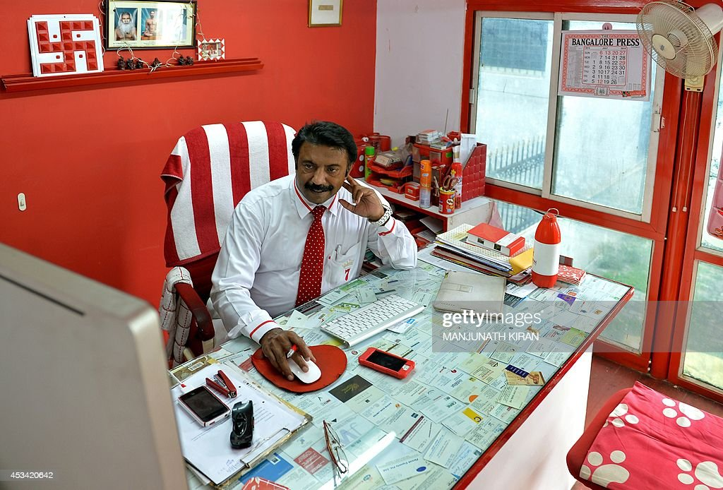 In this photograph taken on July 26, 2014, Indian businessman Sevenraj who has a fixation for the colours red and white works in his office in Bangalore. 52-year-old Sevenraj's fetish for red and white colours started several decades ago with an intention to create a unique identity for himself and a brand image for his real estate agency went on to become a part and parcel of his life, his home and his family. Born as the seventh offspring, his realist father named him 'Sevenraj' and thus the number '7' too has remained his other fixation apart from the 'Red & White' colours. Everything in his house, office, his car are of the two shades. His family dress in red and white too when they go out with Sevenraj. AFP PHOTO/Manjunath KIRAN