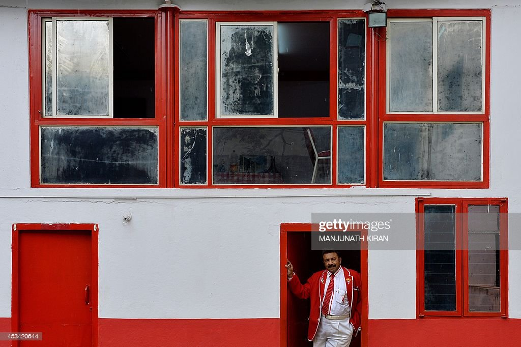 In this photograph taken on July 26, 2014, Indian businessman Sevenraj who has a fixation for the colours red and white poses outside his office in Bangalore. 52-year-old Sevenraj's fetish for red and white colours started several decades ago with an intention to create a unique identity for himself and a brand image for his real estate agency went on to become a part and parcel of his life, his home and his family. Born as the seventh offspring, his realist father named him 'Sevenraj' and thus the number '7' too has remained his other fixation apart from the 'Red & White' colours. Everything in his house, office, his car are of the two shades. His family dress in red and white too when they go out with Sevenraj. AFP PHOTO/Manjunath KIRAN