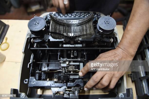 In this photograph taken on July 26 typewriter mechanic Anand Savarkar checks the keys of an old typewriter at his repair shop in Mumbai The...