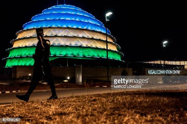 In this photograph taken on July 28 a Rwandan policeman walks past the dome of the Kigali Convention centre as it glows with the colours of the...