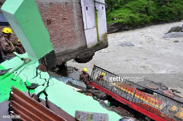 In this photograph taken on July 3 Indian State Disaster Response Force personnel examine the wrealage of a building after monsoon floodwaters...