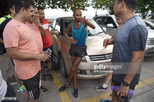 In this photograph taken on July 30 2017 Indian fitness enthusiasts listen to runner Samir Singh during a break in his early morning run in Mumbai...
