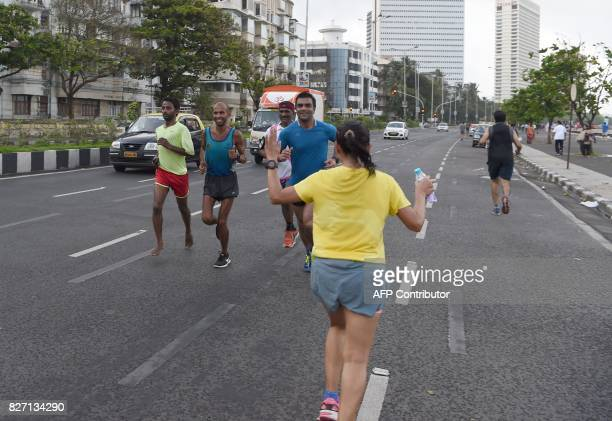 In this photograph taken on July 30 2017 Indian runner Samir Singh is greeted by other runners in Mumbai Tormented by blisters illness and injuries...