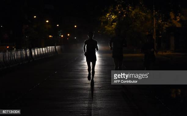TOPSHOT In this photograph taken on July 30 2017 Indian runner Samir Singh is silhoutted by car headlights during his run in the early morning in...