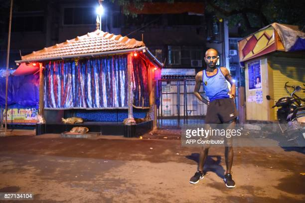 In this photograph taken on July 30 2017 Indian runner Samir Singh stretches before the start of a run in Mumbai Tormented by blisters illness and...