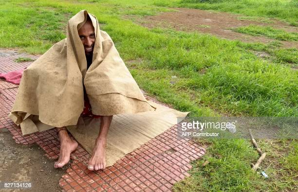 In this photograph taken on July 30 2017 Indian runner Samir Singh covers himself from a sudden downpour as he rests during his early morning run in...