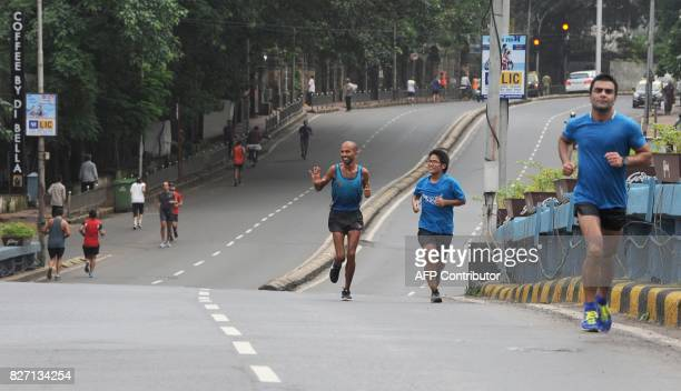 In this photograph taken on July 30 2017 Indian runner Samir Singh waves to other runners in Mumbai Tormented by blisters illness and injuries Indian...
