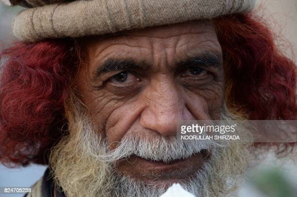 TOPSHOT In this photograph taken on July 30 an elderly Afghan man with his hair dyed with henna looks on as he eats ice cream on the outskirts of...