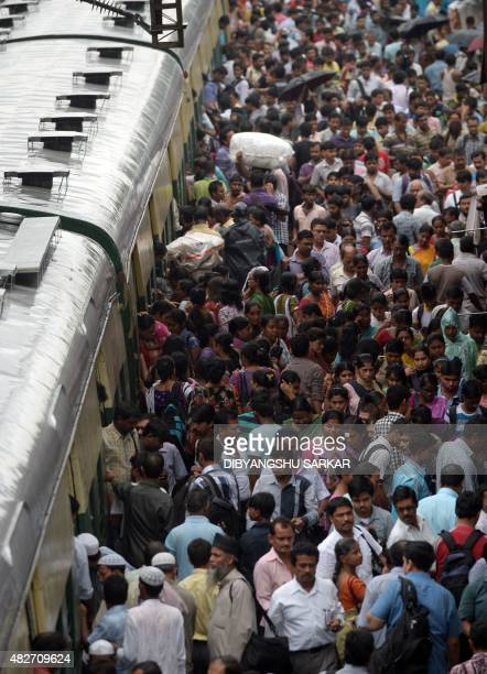 In this photograph taken on July 31 Indian commuters disembark from a local train as they walk on the platform of Bidhannagar Road railway station in...