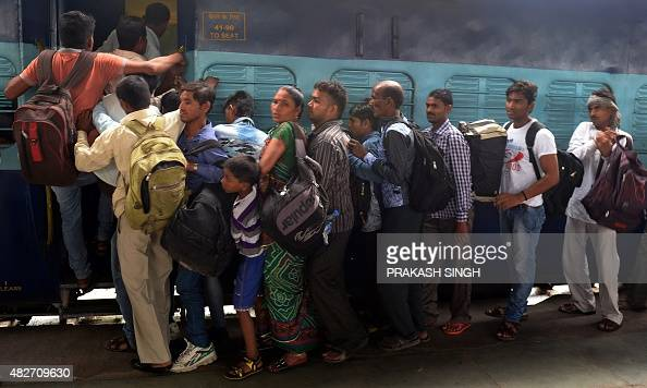 In this photograph taken on July 31 Indian passengers struggle to board an unreserved coach of an Interstate train at a station in New Delhi...
