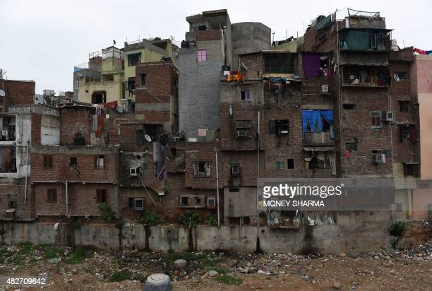 In this photograph taken on July 31 narrow rows of houses back onto ground strewn with rubbish in New Delhi According to a recently released United...