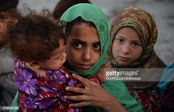 In this photograph taken on July 5 Afghan children who fled from Kot district of the eastern Nangarhar' province following threats from the Islamic...