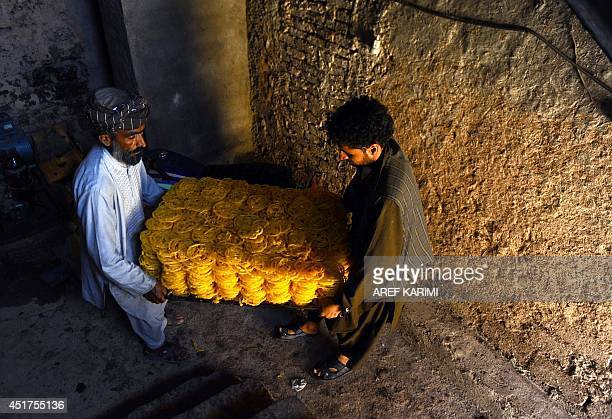 In this photograph taken on July 5 Afghan workers carry sweets at a traditional 'jelabi ' sweet factory during the Islamic holy month of Ramadan in...