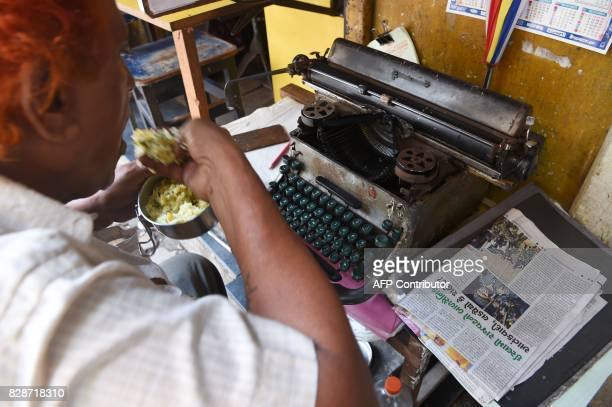 In this photograph taken on July 6 a typist eats lunch at his roadside typing stall in Mumbai The unmistakable chatter of typewriters outside...