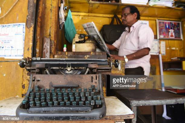 In this photograph taken on July 6 a typist reads a newspaper while waiting for customers at his roadside typing shop in Mumbai The unmistakable...