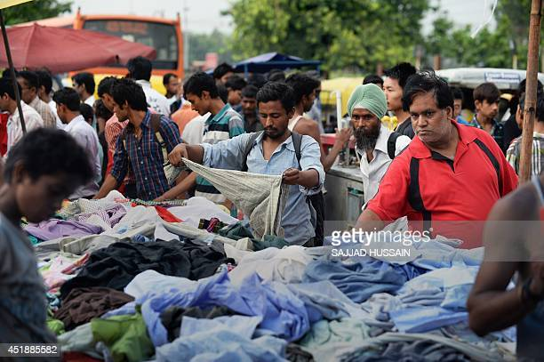 In this photograph taken on July 6 Indian shoppers buy clothes at a Sunday market in the old quarters of New Delhi India's new government is due to...
