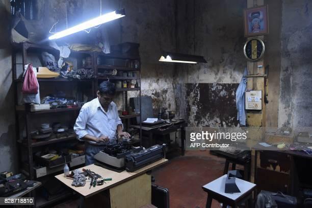 In this photograph taken on July 6 typewriter mechanic Anand Savarkar checks the keys of an old typewriter at his repair shop in Mumbai The...