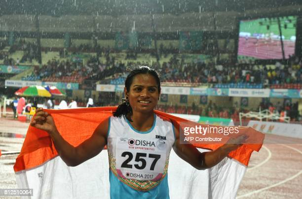 In this photograph taken on July 7 India's Dutee Chand celebrates after placing third in the women's 100m event at the 22nd Asian Athletics...