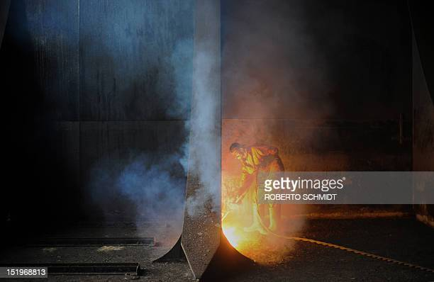 In this photograph taken on July 9 a shipyard worker is enveloped in the fumes coming off a separating wall he is cutting through with his a blow...