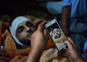In this photograph taken on July 9 Kashmiri mourners take photographs of the body of Burhan Muzaffar Wani the newage poster boy for the rebel...