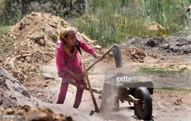In this photograph taken on June 11 twelve year old Indian girl Kavita works at a brick kiln on the outskirts of Jammu on the eve of World Day...