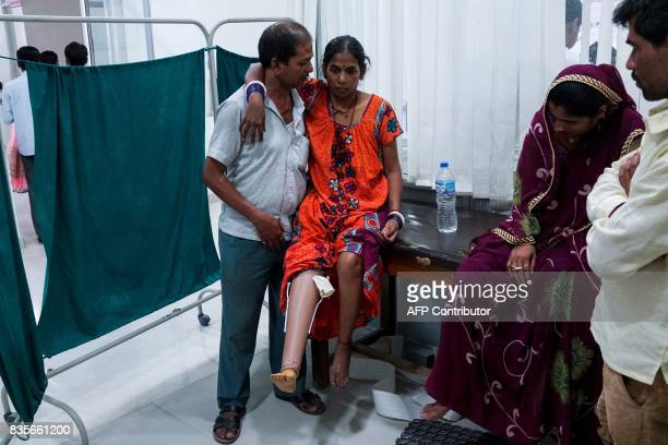 In this photograph taken on June 13 an Indian man helps his wife to walk for the first time with her first rubberbased prosthetic leg at the Bhagwan...