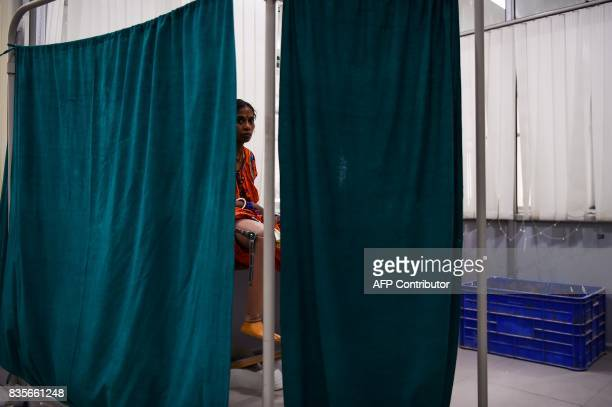 In this photograph taken on June 13 an Indian woman waits for her first rubberbased prosthetic leg at the Bhagwan Mahaveer Viklang Sahayata Samiti...