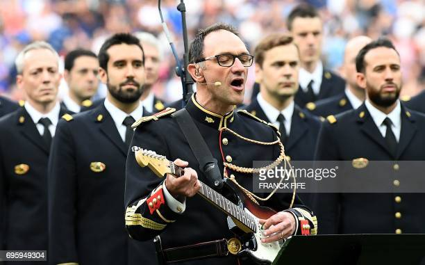 In this photograph taken on June 13 JeanMichel Mekil a gendarme of the Republican Guard sings and plays guitar on the song of British group Oasis...