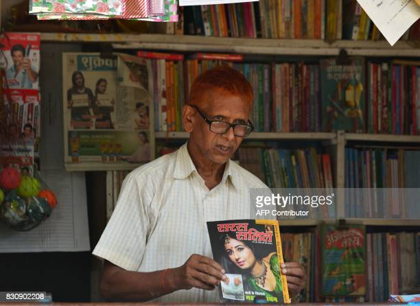 In this photograph taken on June 13 Nepali bookshop keeper Rajendra Kusuwah holds a magazine during an interview with AFP in Janakpur some 300km...