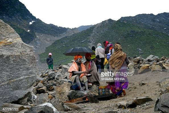 In this photograph taken on June 14 Indian Sadhus gather close to partially restored Kedarnath Temple in the northern state of Uttarakhand nearly two...