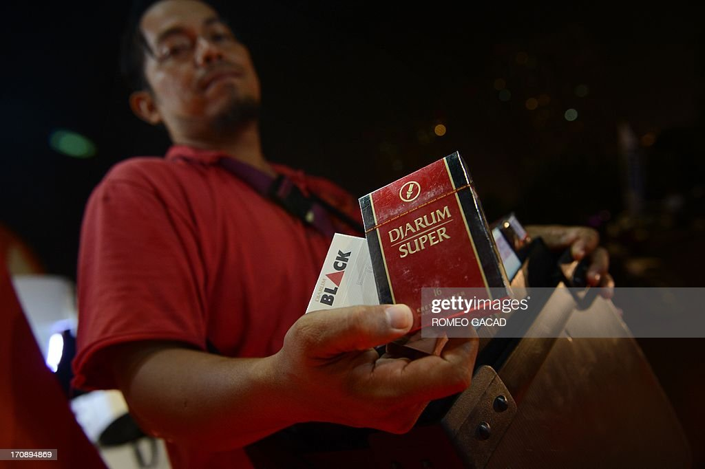 In this photograph taken on June 15, 2013, a vendor sells Djarum tobacco outside the Djarum sponsored Indonesia Open badminton tournament at the Senayan stadium in Jakarta. Djarum, Indonesia's third biggest tobacco company is set to end its nine-year sponsorhip of the tournament, one of the country's top sporting events, as the Badminton World Federation seeks to comply with the policy on tobacco ad bans. While many countries long ago dropped tobacco advertising from sports tournaments, concerts and other cultural events, it is still common in Indonesia. The southeast Asian country has the world's highest percentage of young smokers, according to a World Health Organisation (WHO) report from 2006, which found more than 37 percent of high school and university students smoked while smoking rates have risen six-fold over the last 40 years, with 89 million Indonesians in a population of 240 million smoking today, WHO data shows.
