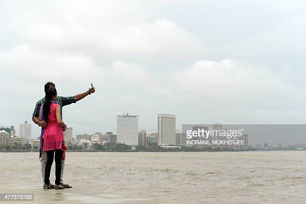 In this photograph taken on June 15 a young Indian couple take a 'selfie' on Marine Drive promenade in Mumbai Selfies have become a global phenomenon...