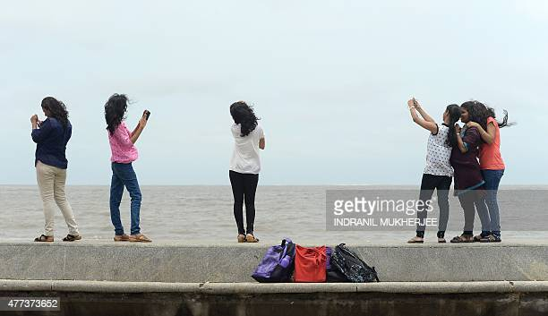 In this photograph taken on June 15 young Indian students take 'selfies' on Marine Drive promenade in Mumbai Selfies have become a global phenomenon...