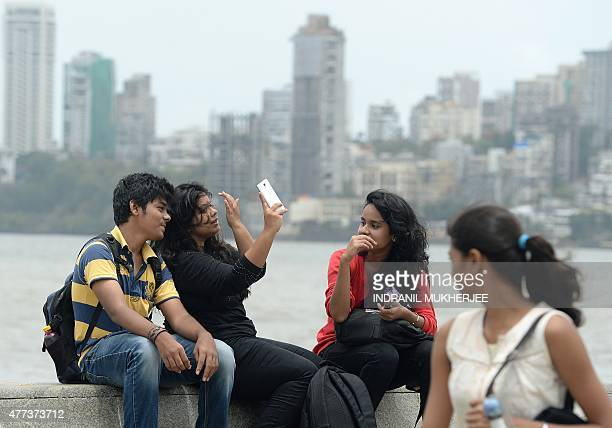 In this photograph taken on June 15 young Indians take a 'selfie' on Marine Drive promenade in Mumbai Selfies have become a global phenomenon with...