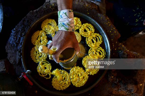 In this photograph taken on June 22 2015 an Afghan labourer works at a traditional 'jelabi' factory during the Islamic holy month of Ramadan in Herat...