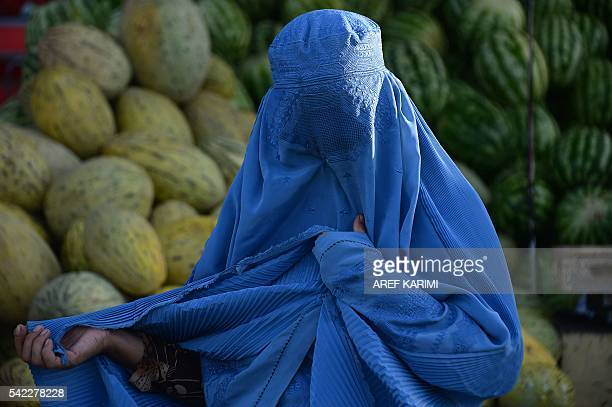 In this photograph taken on June 22 a burqaclad Afghan woman buys fruit at a busy market during the Islamic holy month of Ramadan in Herat province...
