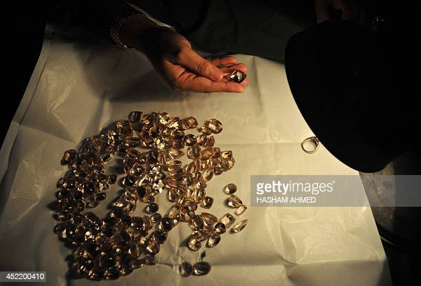 In this photograph taken on June 24 a Pakistani craftsman checks a gemstone at a workshop in Peshawar For 400 years the craftsmen and traders of...