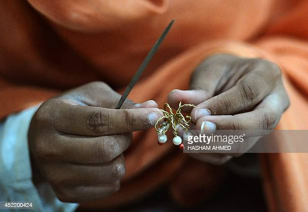 In this photograph taken on June 27 a Pakistani employee prepares a gemstone at a workshop in Peshawar For 400 years the craftsmen and traders of...