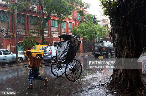 In this photograph taken on June 28 2014 an Indian rikshaw puller transports commuters through heavy monsoon rain in Kolkata Rain fell in several...