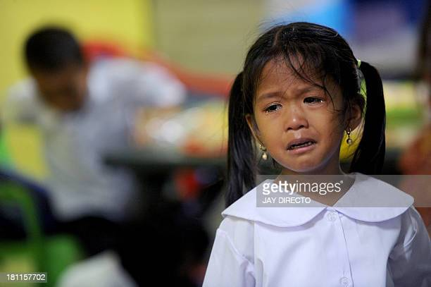 In this photograph taken on June 3 2013 a young student cries as she goes to a government school for the first time in Manila The Philippines is...