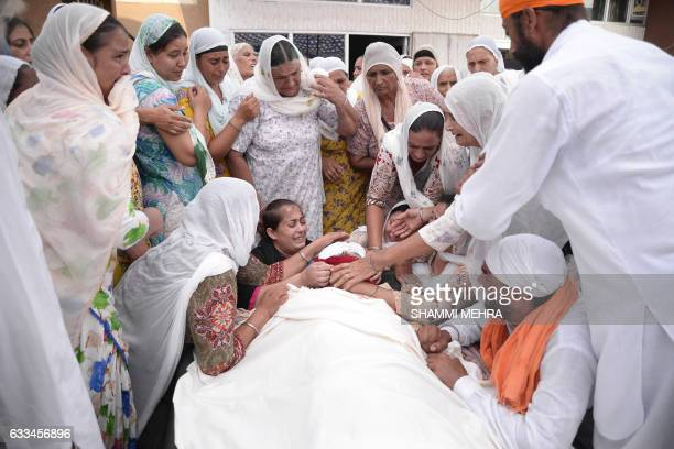 In this photograph taken on June 30 Indian relatives mourn at the funeral of drug addict Jasvir Singh in the village of Kabir Pur Kapurthala District...