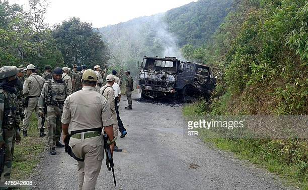In this photograph taken on June 4 Indian security personnel stand alongside the smouldering vehicle wreckage at the scene of an attack on a military...