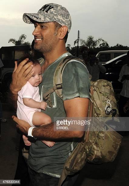 In this photograph taken on June 5 Indian cricket captain Mahendra Singh Dhoni carries his daughter 'Ziva' as they arrive at Birsa Munda...