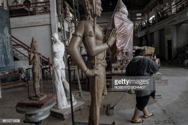 In this photograph taken on March 09 a Thai cleaner mops the floor near figures that will serve as a mold where images just like it will be made to...