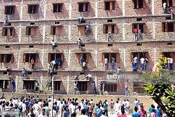 In this photograph taken on March 19 Indian relatives of students taking school exams climb the walls of the exam building to help pass candidates...