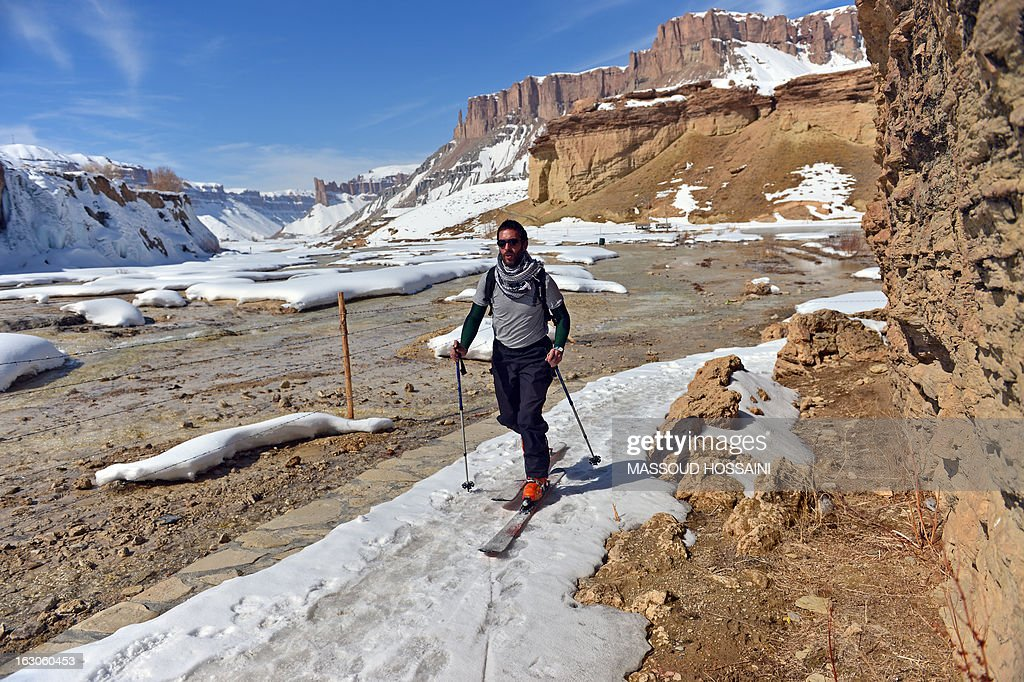 In this photograph taken on March 2, 2013, a foreign tourist skis at the Band-e Amir lake on the outskirts of Bamiyan city. Bamiyan, some 200 kilometres (124 miles) northwest of Kabul, stands in a deep green and lush valley stretching 100 kilometres through central Afghanistan, on the former Silk Road that once linked China with Central Asia and beyond. The town was home to two nearly 2,000-year-old Buddha statues before they were destroyed by the Taliban, months before their regime was toppled in a US-led invasion in late 2001. AFP PHOTO / Massoud HOSSAINI