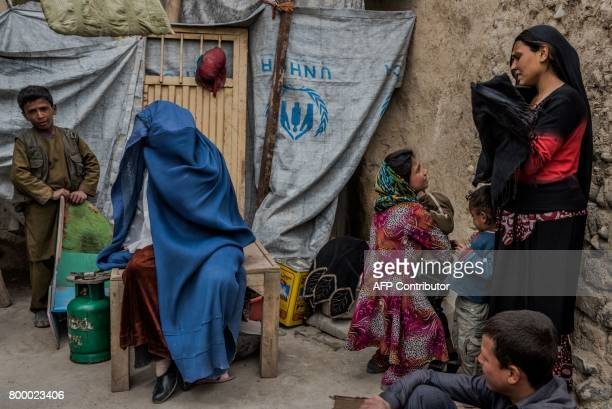 TOPSHOT In this photograph taken on March 20 Afghan widow Nawzi Fakiri speaks during an interview with AFP at her home alongside members of a...
