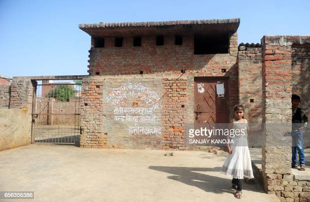 In this photograph taken on March 21 Indian children play outside a closed illegal slaughter house at Naini in Allahabad on March 21 2017 Indian...