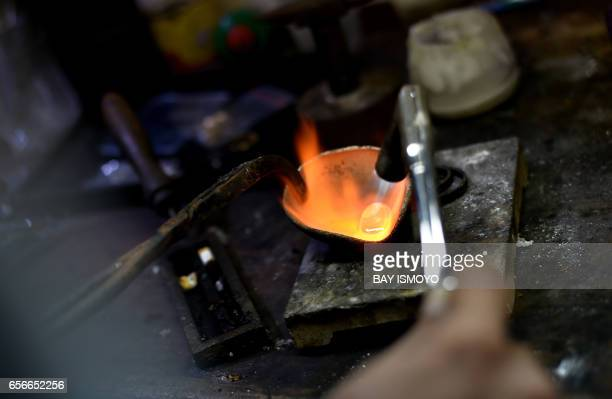 TOPSHOT In this photograph taken on March 22 2017 an Indonesian goldsmith melts gold at his workshop in Jakarta before pouring it into a mold A...